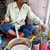 Chai seller. Mathura.  With that bottle in his left hand he is grinding fresh ginger for the pot and that addition was why his was the best we tried.