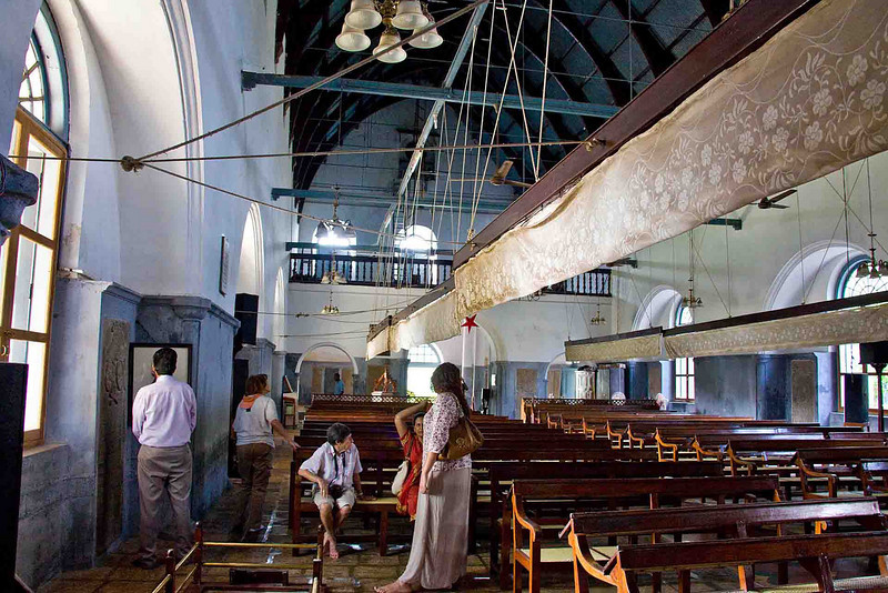 Vasco da Gama's burial plot is in the little brass enclosure in the left foreground. The cloth hangings are fans, operated by pulling on the horizontal ropes. The ropes go through the walls and were pulled by fan operators pulling down on the ropes, like bell-pullers, on the outside of the wall.