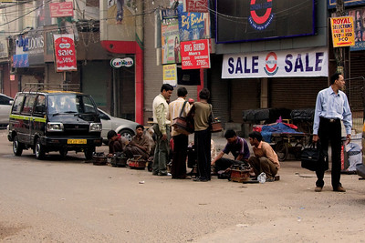The shoe shiners sleep on the street next to their tools of trade, they were preparing for a new day when we passed them on a street in Karol Gagh; New Delhi.  Photographed February 2009 - © 2009 Lesley Bray Photography - All Rights Reserved.