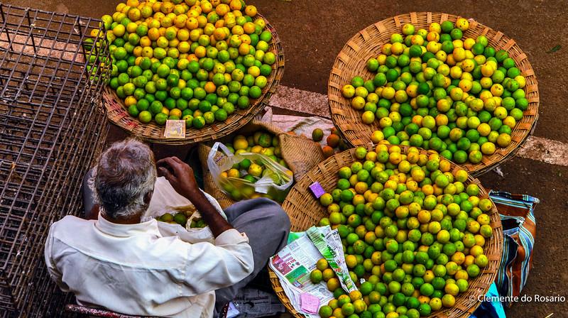 Vendor at Mapusa Market selling green limes,Mapusa, Goa,India