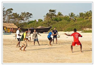 Youths playing soccer on Varca Beach, Salcette Goa, India