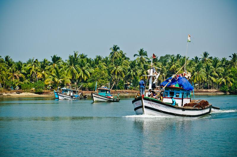 Fishing Trawlers cruising the River Sal in Mobor, South Goa India