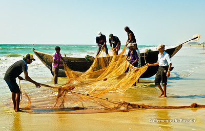 Fishermen putting away the fishing net, Varca Beach, Goa, India