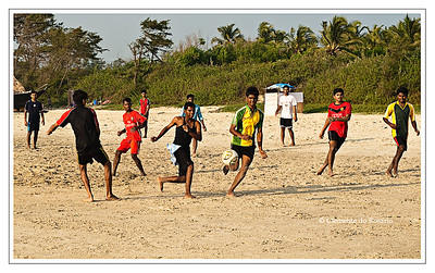 Youth playing soccer on Varca Beach, Goa, India