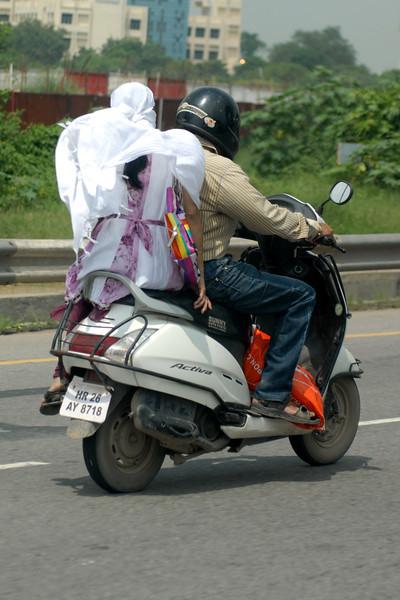 Side saddle on a scooter.