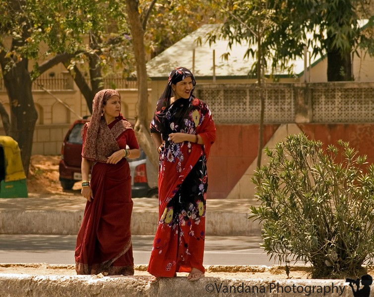 On the roads in New Delhi. - two very young women in sarees wait to cross the road.