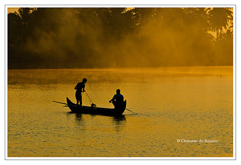 Fishermen silhouetted against the golden light of dawn in the backwaters of Kerala, India<br /> File Ref: Kerala-2006 165R