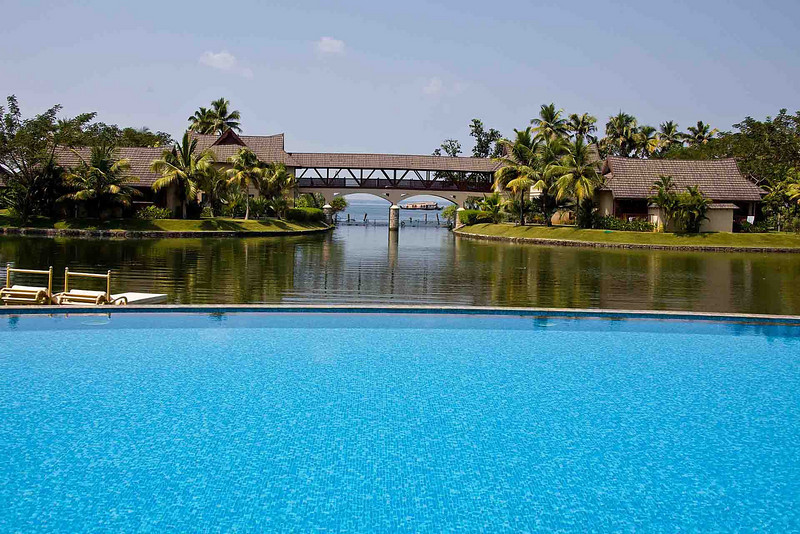 Infinity swimming pool in the foreground; lagoon and passage to Vembanad Lake that covers many square miles. Houseboat is passing the gates to the lake.