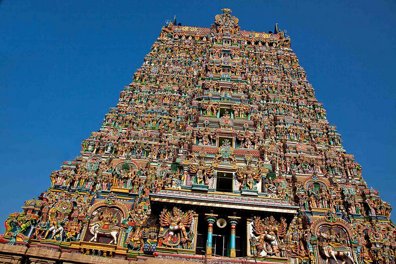 """Sri Meenakshi Temple from across the street. It has five towers; the other four somewhat smaller than this one, but they are equally ornate. The temple is a square covering 17 acres. It is dedicated to the three-breasted, fish-eyed goddess Meenakshi, and it is considered to be the absolute epitome of Hindu architecture. (""""Fish-eye"""" in Hindu lore is supposed to mean """"perfect eyes."""") This tower is 170 feet tall and has thousands of figures on its four faces. The legend is that the third breast would go away when Meenakshi met her husband, and so it did when she met Shiva. The temple dates to 1560. It was its natural beige color until 1960 when it was painted as you see it today. It is completely refurbished every 12 years. The last refurbishment was in 2009."""