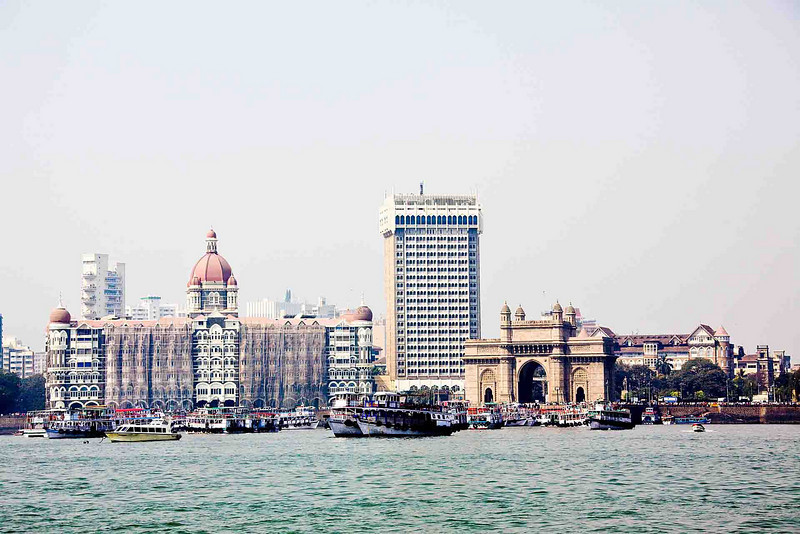 Taj Mahal Hotel (on left), sill being repaired and still closed after the 2008 terrorist attack. The new Taj hotel is the tall building in the center. It is fully operational, with very stringent security. Gateway of India to the right, below the new Taj.