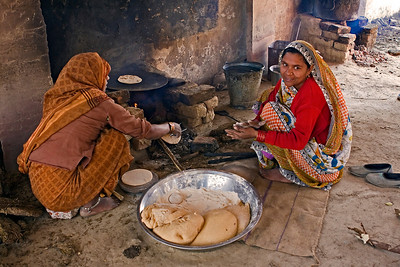Mothers cooking chipaties at the village school to feed the children.  It is part of a program to ensure all school children receive food daily.  We have similar programs in Australia.