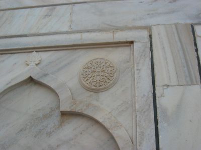 Each panel of white marble on the exterior is a carved arch with a medallion on either side.