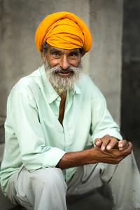 An elderly Sikh man sits on a village street corner.