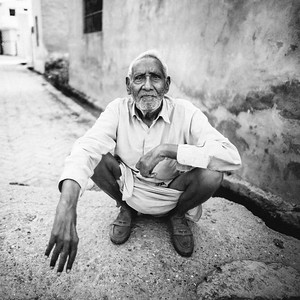 A elderly man rests on a village road.