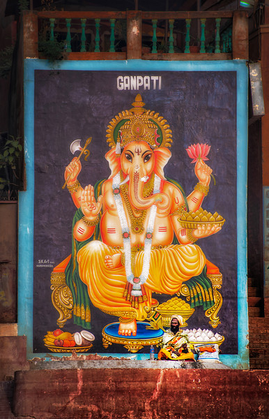 Large painting of Ganesha on a building along the Ganges in Varanasi. A local sadhu (wandering holy man) sits in the lower right corner and blends into the scene.