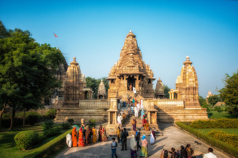 Early morning visitors at the main Khajuraho temple. As usual the women prefer the colorful Indian dress, while men prefer western style clothing.