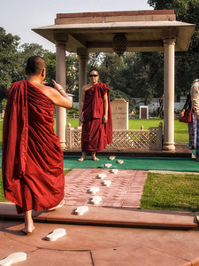 Two Buddhist monks on vacation. The site is where Gandhi died. The footsteps mark his steps after he had been shot to the location of his death.