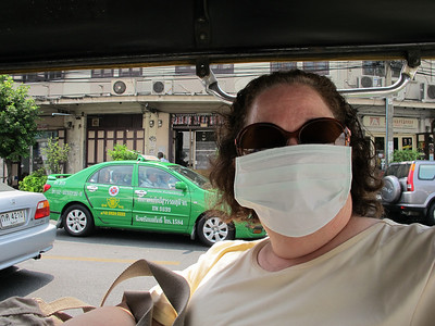 Renee Mirsky modeling a surgical face mask while seated in a Tuk-Tuk in Bangkok.