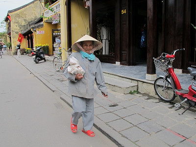 Older resident in Dayglo flip flops in the streets in Hoi An.