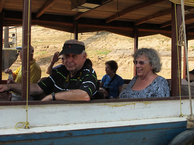 Harry and Linda Weber aboard a motorized watercraft that will cruise an inlet into Tonle Sap Lake.  Behind them is Arnie Kaston Stu Dublinske (waiving), and Linda Shyavitz.