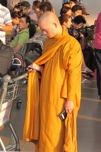 A monk in the airport at Saigon checks his  email.