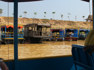 Boats in queue waiting to be summoned to take passengers into Tonle Sap Lake.  This canal was dredged from just outside Siem Reap to Tonle Sap Lake so that fishing boats and tourist boats have access to Siem Reap in the dry season.    This area, during the rainy season, is covered with about eight meters of water and the lake becomes one of the largest fresh water lake in Southeast Asia.  All of the fishermen living in shanties along the canal must move every month to higher ground during the rainy season as the water rises.  The water level will eventually rise above the tree levels in the photos.  Some of the trees have adapted to this phenomenon, remain alive under water, and still produce fruit during the dry season.  The canal is not polluted but there was silt on the bottom that made it look very dirty.  We saw children swimming in the canal and fishermen seining for fish so it probably is not as bad as it looks.  The floating city was amazing.  About 800 families live in this village.  There is a big school with a basketball court, a Catholic church, a grocery store, several restaurants and of course many houses…all on boats.  Electricity is supplied by automobile batteries that must be recharged twice a week.  If you look closely at the photos, you will spot satellite dishes or TV antennae.  There are people selling beer, bottled water, frits and almost anything else from their boats that attempt to come aside your sightseeing boat.  And there are people begging from their boats.  Read more: http://www.travelpod.com/travel-blog-entries/thewrens/2/1302802849/tpod.html#ixzz1KSFl2Xq9