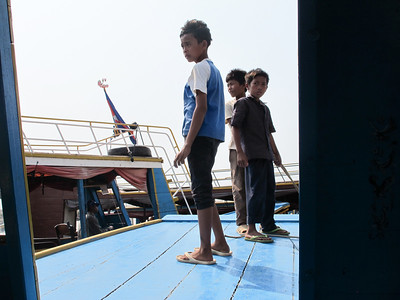 Tonle Sap Lake -- The Floating City near Siem Reap  See http://upload.wikimedia.org/wikipedia/commons/3/3a/TonleSapMap.png for a map of the lake.  Young boys who worked the boats on the lake cruise to the floating city.  The older boy (taller, in a blue and white shirt standing to the left) is 14 years old.  His brother (right-most) is 10.  It's possible (probable) that their father or some family member drives/owns the boat.  They assist in docking, loading, unloading, managing the shades alongside the boat, etc.  Very pleasant youngsters, but obviously not enjoying a carefree childhood.  These boys are working.