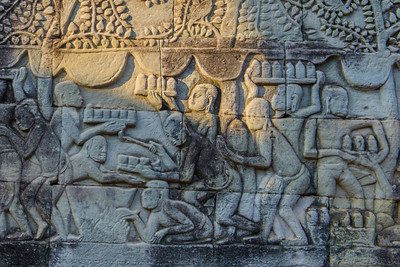 The massive walls are covered with scenes of life of the Khmer. On the south wall is a scene  showing men being served food made in a field kitchen.
