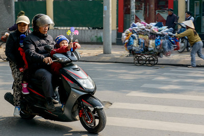 Families of 4 or even 5 often ride on the scooters together. Note the little boy with the windmill.