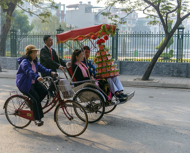 The couple in the cyclo, holding gifts, are on their way to an engagement ceremony.  A number of couples came by as we watched.