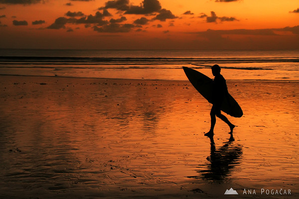 A lone surfer at sunset on the Kuta beach
