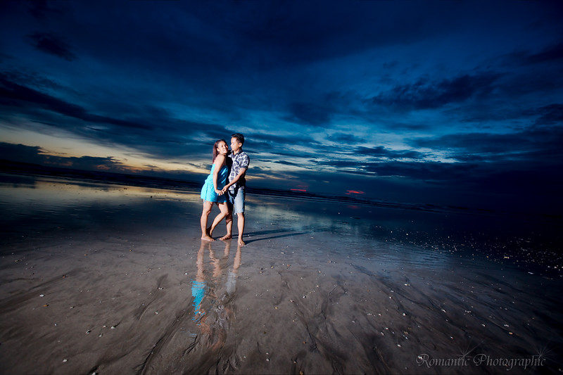 An Indonesian couple  poses in front of a typical Bali sunset.