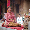A woman sits patiently waiting for an event in the temple complex.