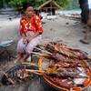 A beach vendor prepares the catch of the day.