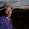 A rice farmer poses for a photo at sunset.