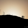 A couple climbs a hill to watch the sun rise.