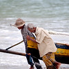 An old man helps a fisherman haul his boat up the shore.