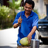 A vendor prepares a refreshing coconut drink in downtown Sabang.