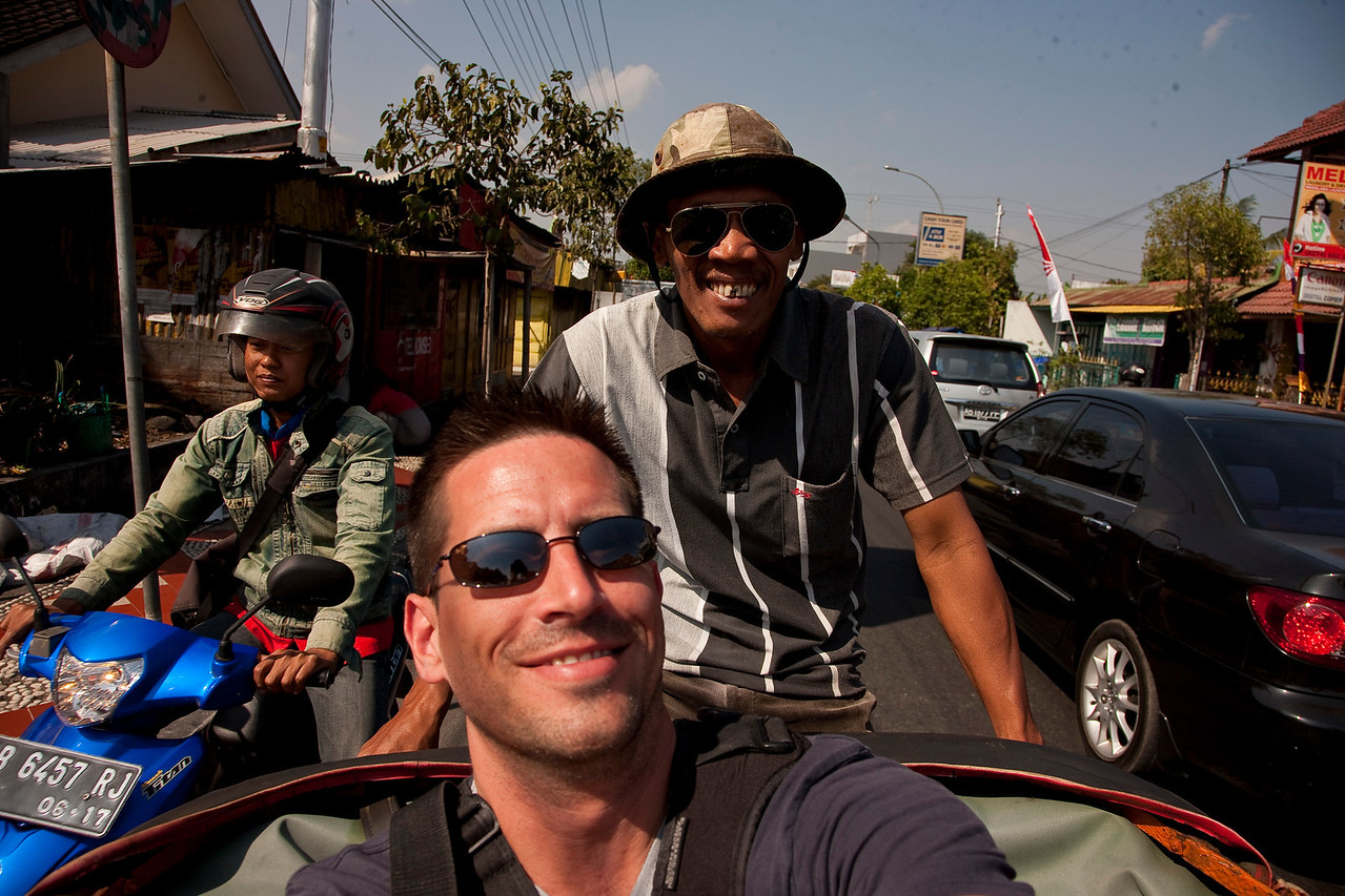 Yogyakarta, in my becak (Indonesian rickshaw). This guy offered to take me to see some of the sights in the city. I said I wanted to go to the walled city, then to the bird market, and then back to my hostel. He opened the bidding with 40,000 rupiah. Whoa, whoa, WHOA, I thought. What is this guy, some kind of crook?! He only has to pedal seven kilometers; I don't think it's worth THAT much. I countered with 20,000. We finally settled on 30,000. I suppose I should mention that 30,000 rupiah is roughly the equivalent of three dollars. It's a peculiar feeling, the moment you realize how indignant you were at the thought of paying $4 instead of $3 to sit on your rear end while some guy pedals you around for seven kilometers.