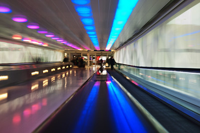 I love these types of tunnels, usually found at airports.  Long walkways with streaming lights and colors.  I always go for the long exposure, hand rail point of view.