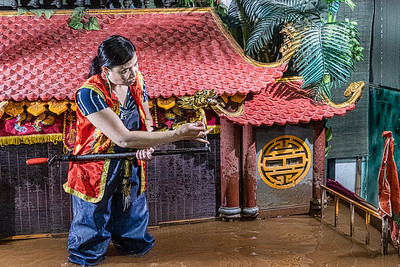 She teachers school children about the tradition of water puppets