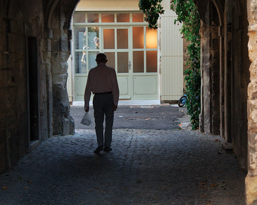 An elderly man strolls home in Avignon, France