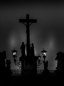 Silhouettes of a cross and statues