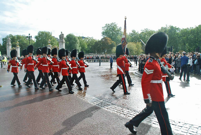 The Queen's Guards arrive at Buckingham Palace lead by their standard flag.
