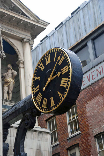 """A clock on St Dunstan-in-the-West Church on Fleet Street.  The statue (above the clock) is one of two """"giants"""" who strike a bell on the hour and quarter hours.  This is the first public clock in London to have a minute hand."""