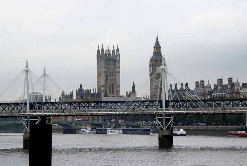 Hungerford Bridge (a railway bridge) has two pedestrian bridges on either side (Golden Jubilee Bridges) supported by cables.  Parliament and Big Ben in the background.