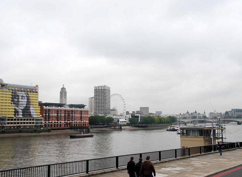 The London Eye as seen from the north bank of the Thames.  The OXO Tower (red building) and Sea Containers Building (with an image of a girl), an office building, are also visible.