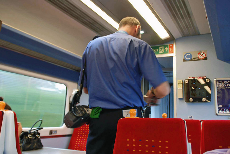 The train conductor checking tickets on the way to the British Nationals in Sheffield, England.
