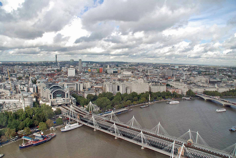 A view from the London Eye of Charing Cross Station, Hungerford Bridge (railway) with the Golden Jubilee Bridges on either side.  The bridge on the far right is Waterloo Bridge.
