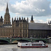 A tour boat on the Thames by the Westminster Bridge.